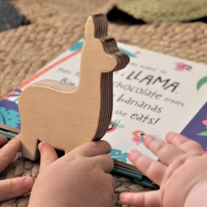 Hand cut birch ply wood llama shelfies held by two toddlers