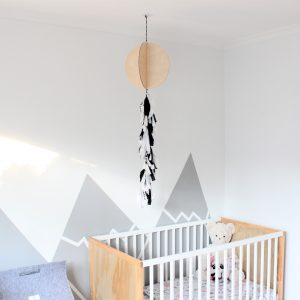 Large birch plywood timber tassel balloon with monochrome safari print tassel hanging over a cot in a baby's nursery