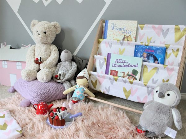 Teddy bears tea party scene in from of a pink, gold and grey love heart book sling