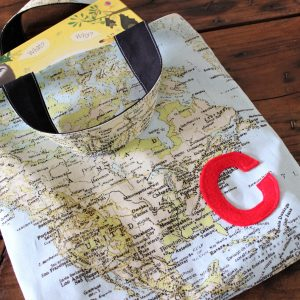 "Map print cotton library bag with red felt ""C"" personalisation on a timber table"