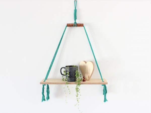Teal cotton macrame cord and birch plywood shelves with copper accent styled with a hand cut birch plywood heart shelfie and a string of pearls succulent in a navy vintage mug