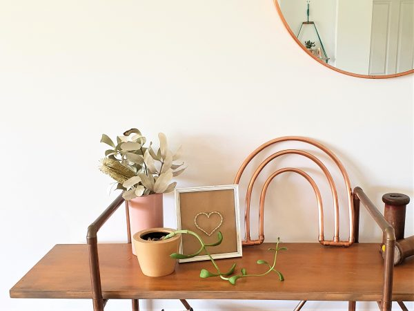 Copper rainbow sitting on a shelf with a pink vase