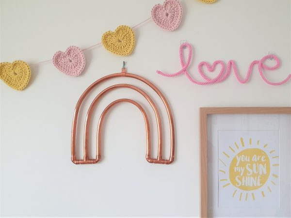 Copper rainbow hanging on the wall with yellow and pink decor