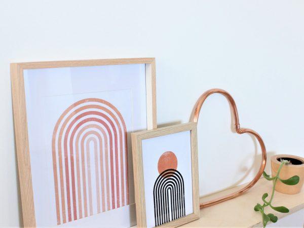 Copper heart sitting on a shelf with boho artworks