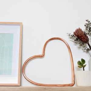 Copper heart sitting on a shelf with mint green decor