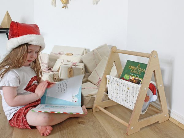 Girl reading in front of a white book caddy with gold and silver stars