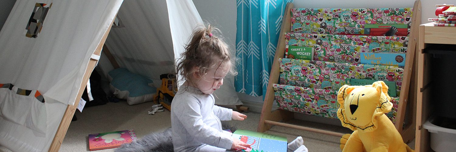Smiling toddler girl reading a book in a nursery with a monster print book sling and lion teddy